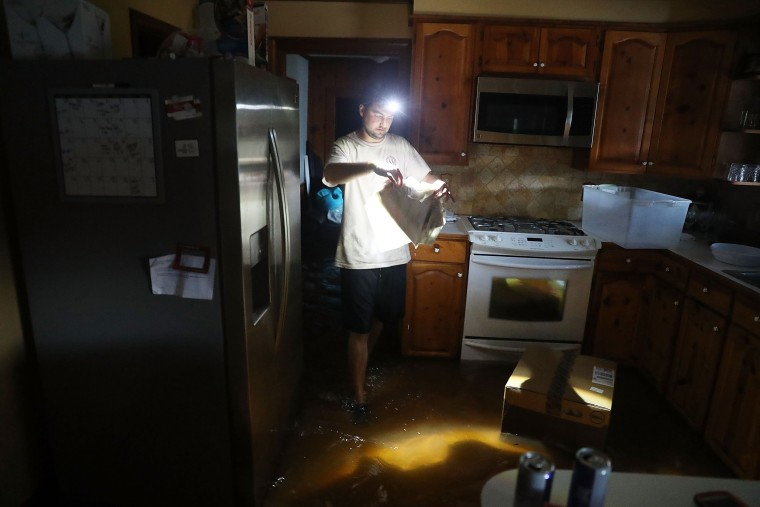 Image: Tommy Gallagher retrieves items from his flooded home on Aug. 17,  in Sorrento, Louisiana.  Last week Louisiana was overwhelmed with flood water causing at least twelve deaths and thousands of homes damaged by the flood waters.