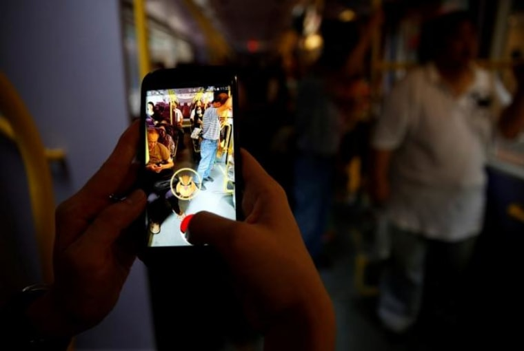 """A passenger plays the augmented reality mobile game """"Pokemon Go"""" by Nintendo inside a bus in Hong Kong, China"""