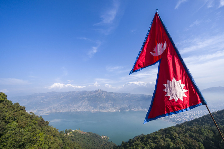The nepali national flag is weaving high above the Phewa