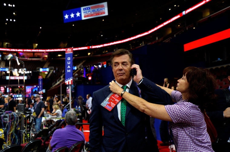 Image: Kathleen Manafort tries to put a credential on her husband Paul Manafort, campaign manager to Republican Presidential Candidate Donald Trump, as he talks on the phone from the floor of the Republican National Convention in Cleveland