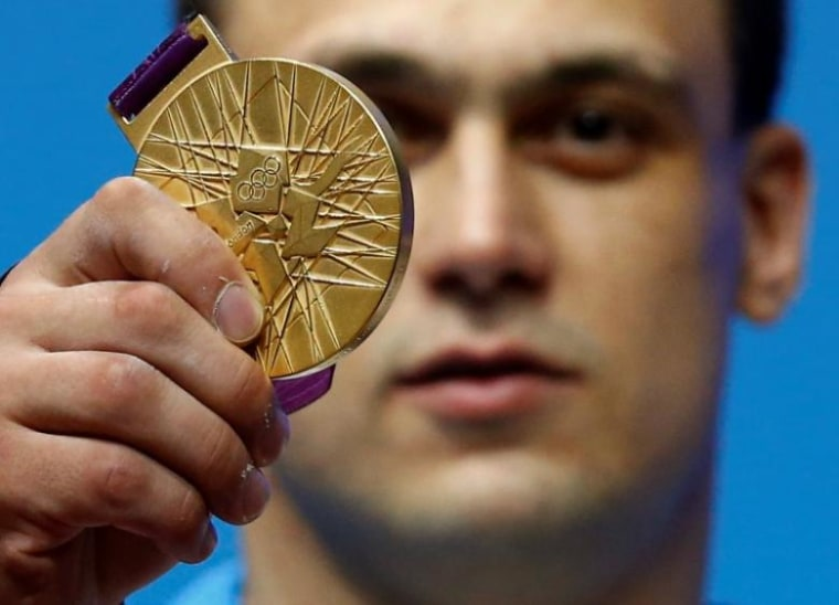 Kazakhstan's Ilya Ilyin poses with his gold medal of the men's 94Kg weightlifting competition at the ExCel venue at the London 2012 Olympic Games
