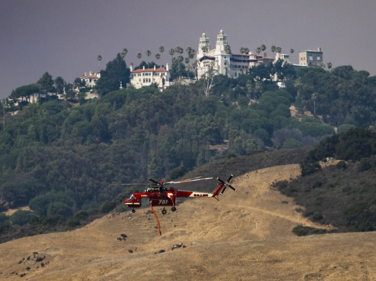Image: A helicopter flies past Hearst Castle