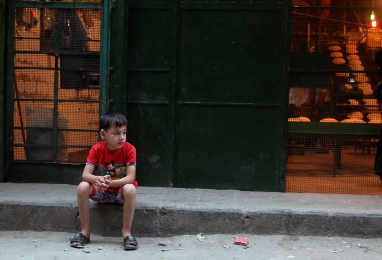 Image: A boy sits outside a bakery in the rebel held al-Shaar neighbourhood of Alepp