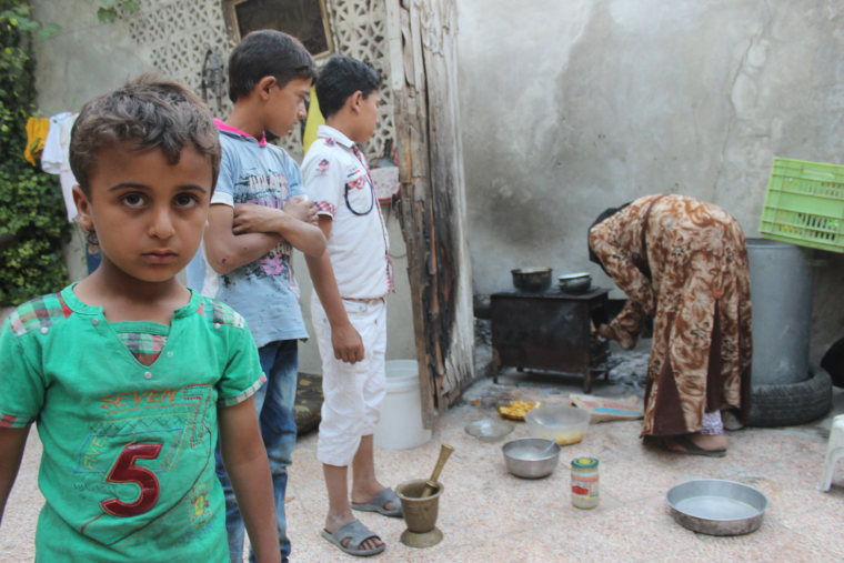 Image: These children have lost their father bombardment and their mother remained miserable and cook them food burning cardboard and plastic