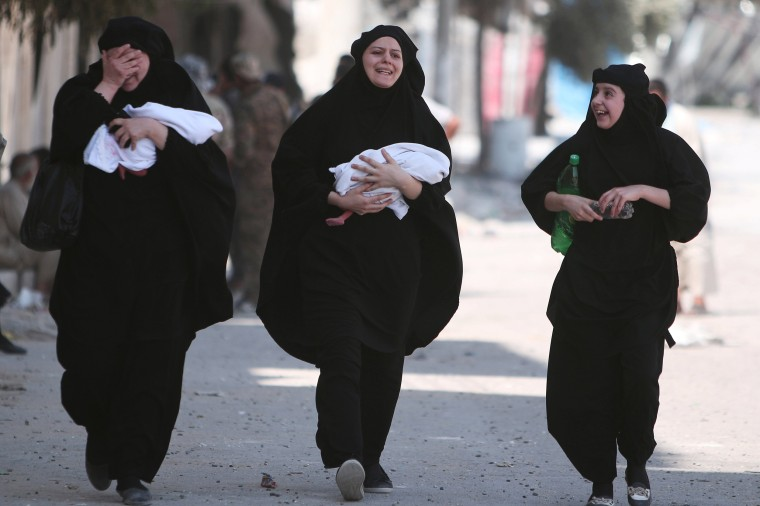 Image: Women carry newborn babies while reacting after they were evacuated by the Syria Democratic Forces (SDF) fighters from an Islamic State-controlled neighbourhood of Manbij
