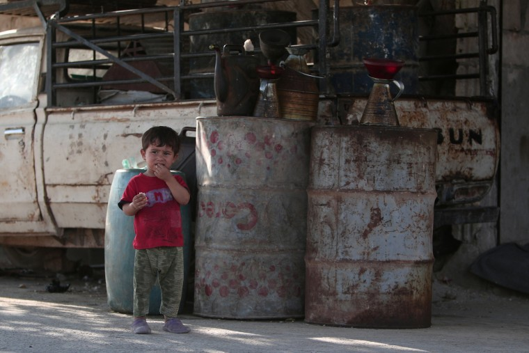 Image: A boy stands near fuel containers in Manbij, in Aleppo Governorate