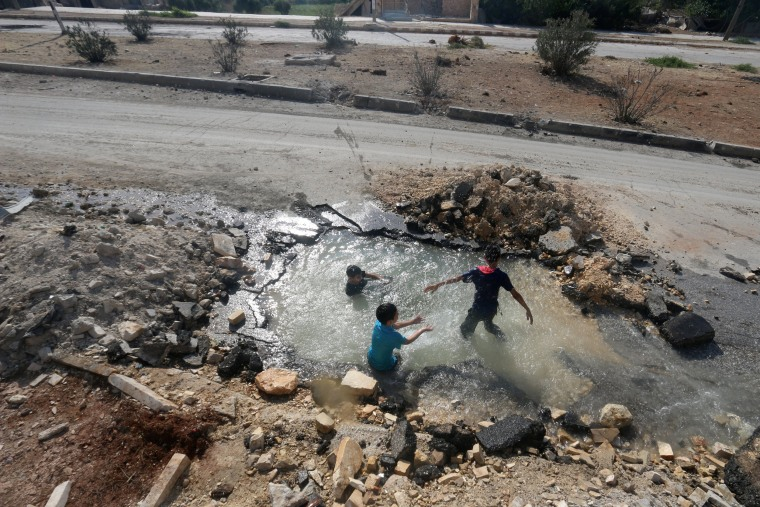 Image: Boys cool down with water from a damaged water pipe due to shelling in the rebel held neighbourhood of Sheikh Saeed