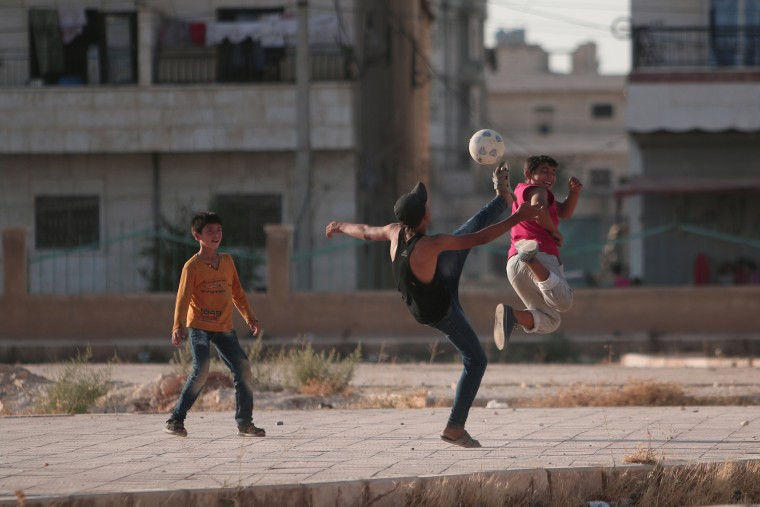 Image: Youths play soccer on a street in Manbij, in Aleppo Governorate