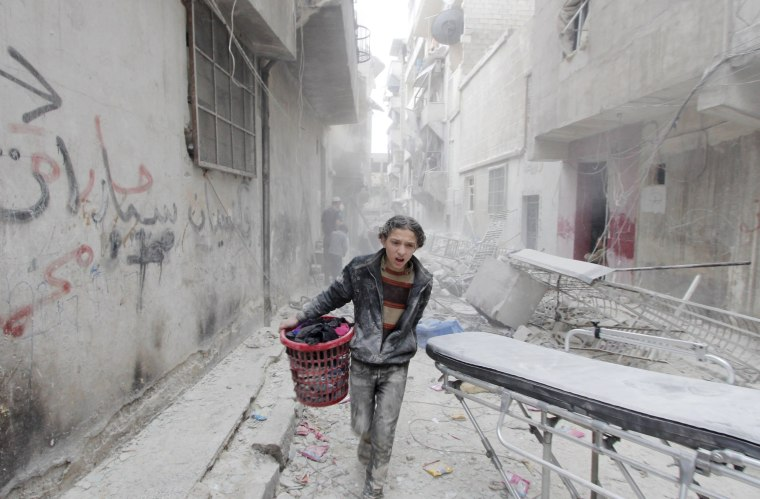 Image: A boy carries his belongings at a site hit by what activists said was a barrel bomb dropped by forces loyal to Syria's President Bashar al-Assad in Aleppo's al-Fardous district