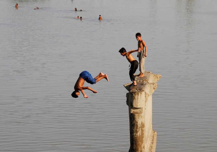Image: Children play as they jump is the Sardaryab River at Charsadda, on the outskirts of Peshawar,