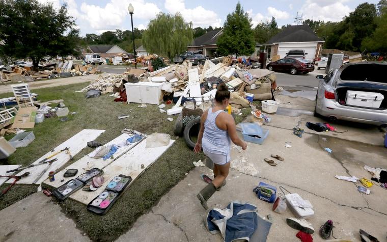 Image: Sheryl Howard walks through her flood damaged frontyard at the South Point subdivision in Denham Springs