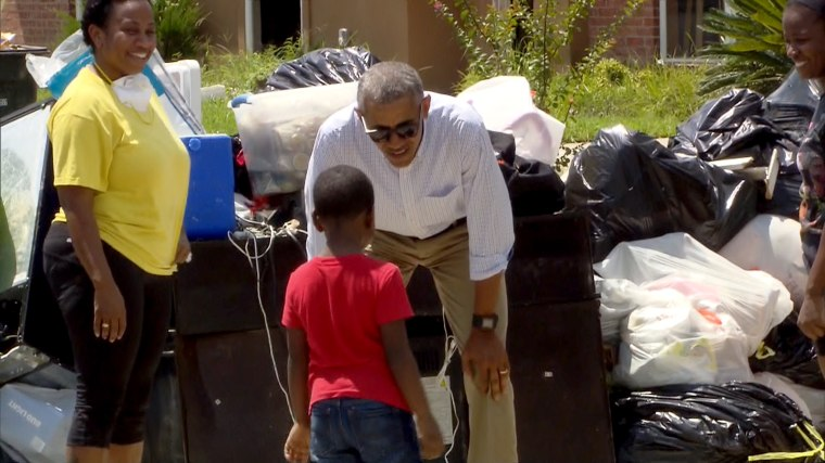 President Barack Obama meets a young resident of Louisiana as he tours flood damage.
