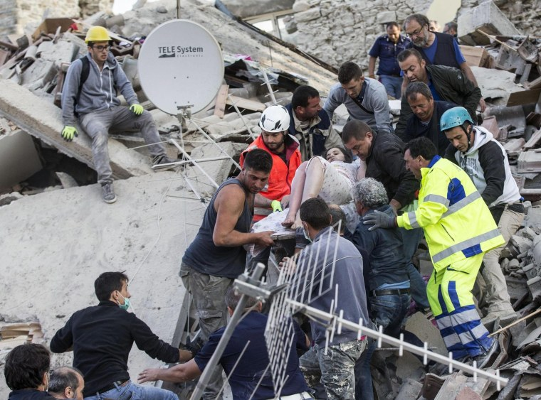 Rescuers carry an injured woman amid the rubble in Amatrice