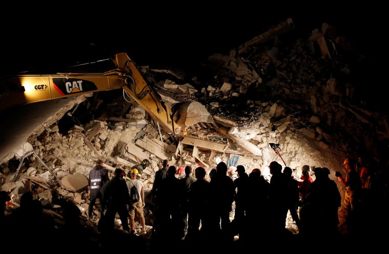 Image: Rescuers work in the night at a collapsed house following an earthquake in Pescara del Tronto