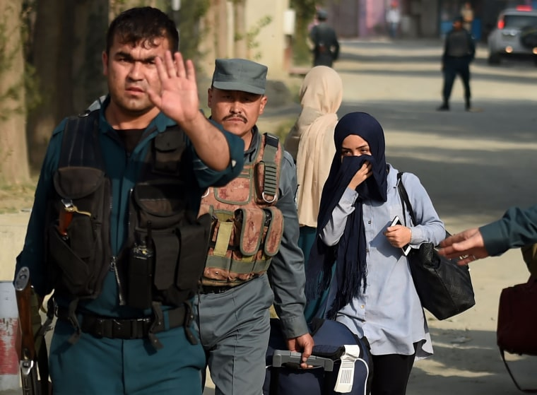 Image: A student who had been trapped inside the American University of Afghanistan during the attack is escorted out by police