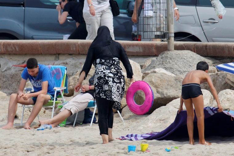 Image: A Muslim woman wears a burkini on a beach in Marseille