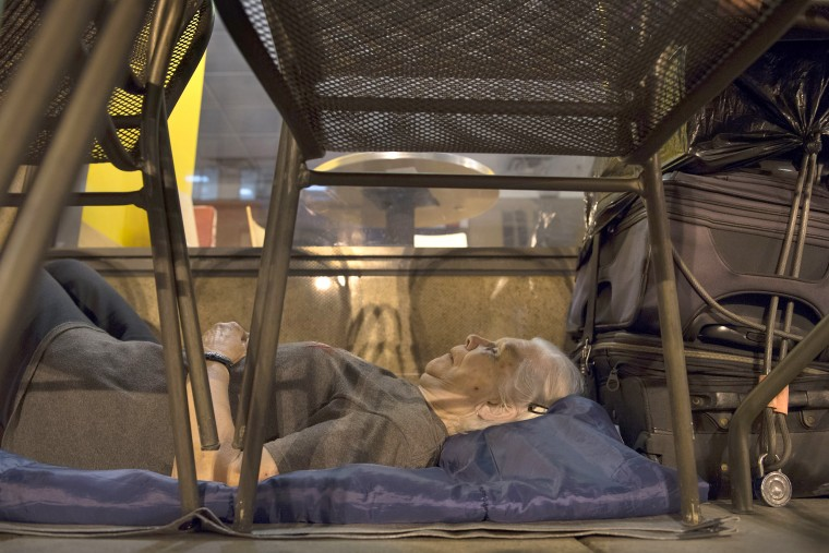 With suitcases in arms reach, Wanda Witter, who is homeless, beds down in her sleeping spot outside the Au Bon Pain on 13th and G Street in Washington. Witter, 80, was recently attacked at the location, suffering a black eye and two stitches. For 20 years she's carried suitcases full of paperwork that she says proves that Social Security owes her $93,000. A lawyer is working with her to get her money back.