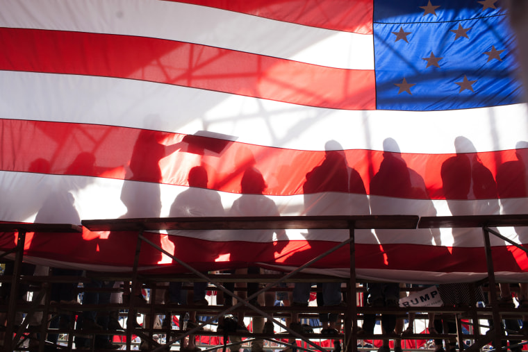Image: Trump supporters are seen backstage through an American flag