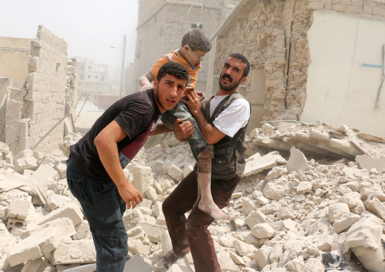 Image: Syrians carry a wounded child in the rubble of buildings