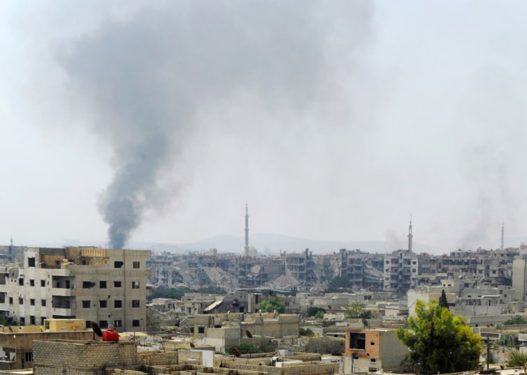 Image: Smoke rises from the besieged Damascus suburb of Daraya, before rebels and residents start being evacuated under an agreement reached on Thursday between rebels and Syria's army