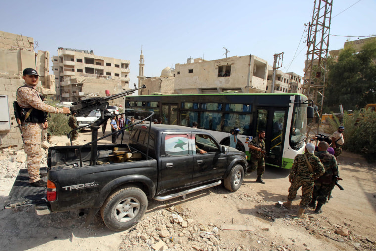 Image: Syrian government troops stand guard as a bus carrying people drives by