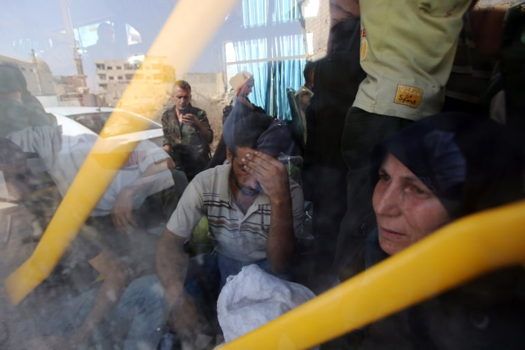 Image: People are seen inside a bus, as they are being evacuated from the town of Daraya