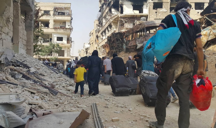 Image: Syrian citizens carry their belonging as they prepare to evacuate from Daraya