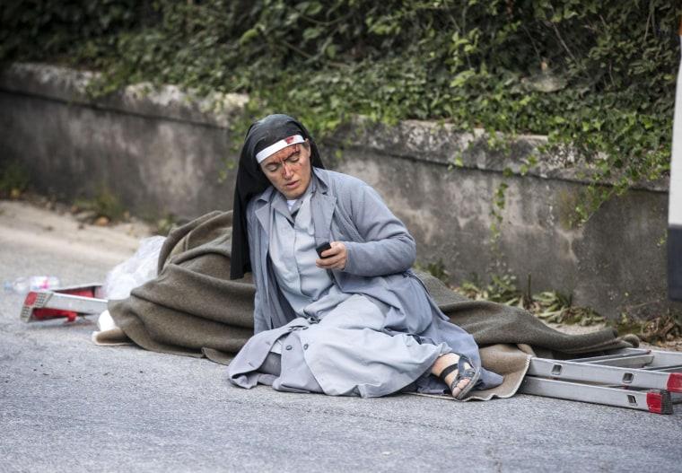 Image: Sister Mariana checks her mobile phone as she lies near a victim laid on a ladder following an earthquake