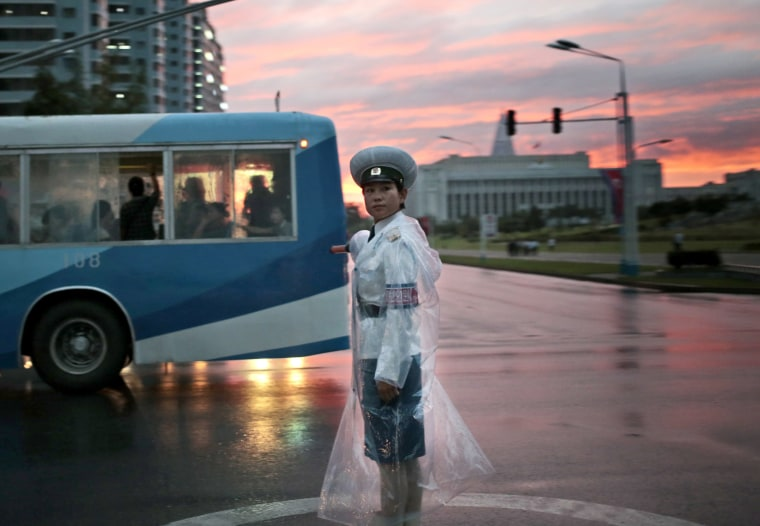 Image: A traffic police officer directs vehicles at a street junction during sunset in Pyongyang