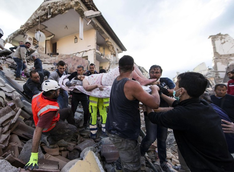 Image: A rescued woman is carried away on a stretcher following an earthquake in Amatrice, Italy