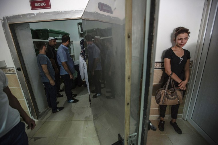 Image: A woman cries at the morgue as she waits for the coffin of her relative