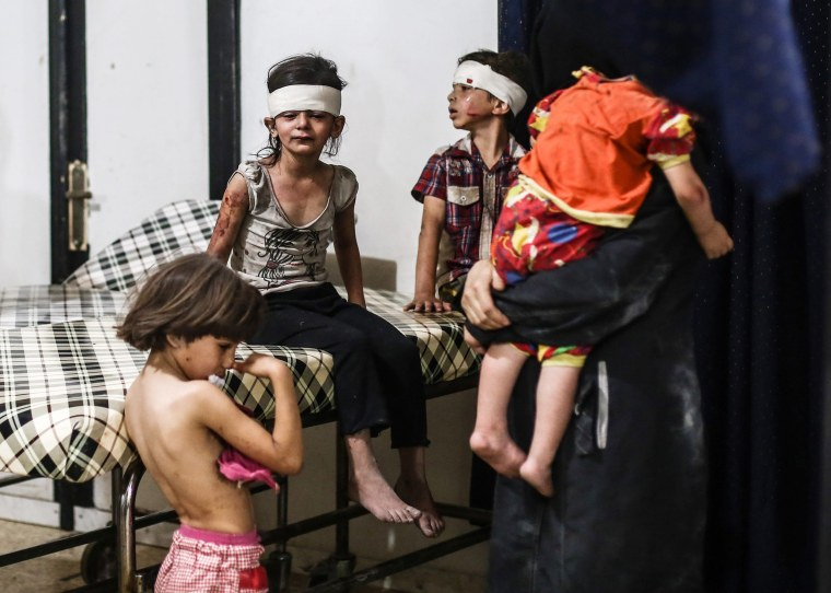 Image: Syrian children reacts after receiving medical attention after an airstrike attack on Douma