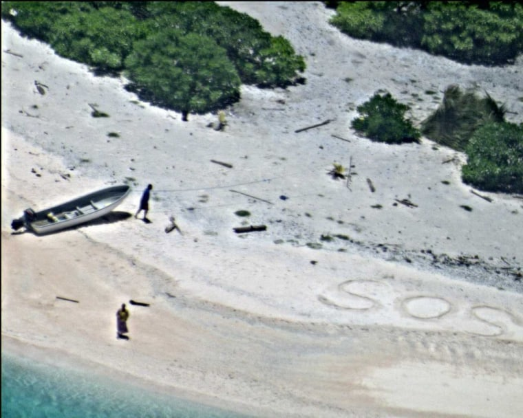 "A pair of stranded mariners signal for help by writing ""SOS"" in the sand."