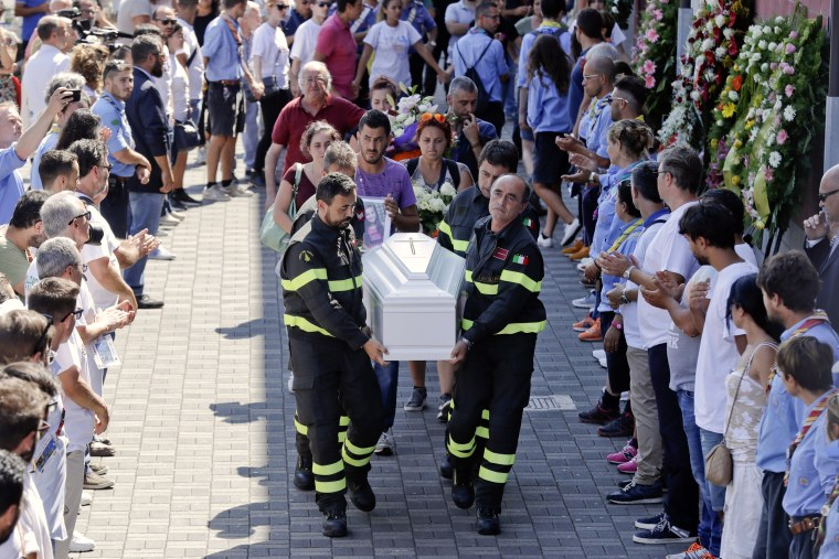 Image: Firefighters carry the coffin of 9-year-old Giulia Rinaldo