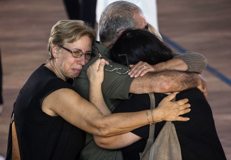 Image: Earthquake victim relatives embrace each other before the funeral