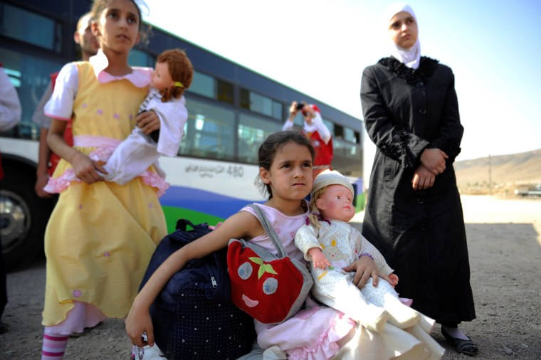 Image: Girls that were evacuated from the besieged Damascus suburb of Daraya arrive to a camp inside the government controlled Herjalleh suburb of Damascus