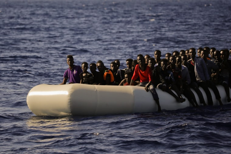 Image: Migrants fleeing Libya on board of a dinghy wait to be rescued