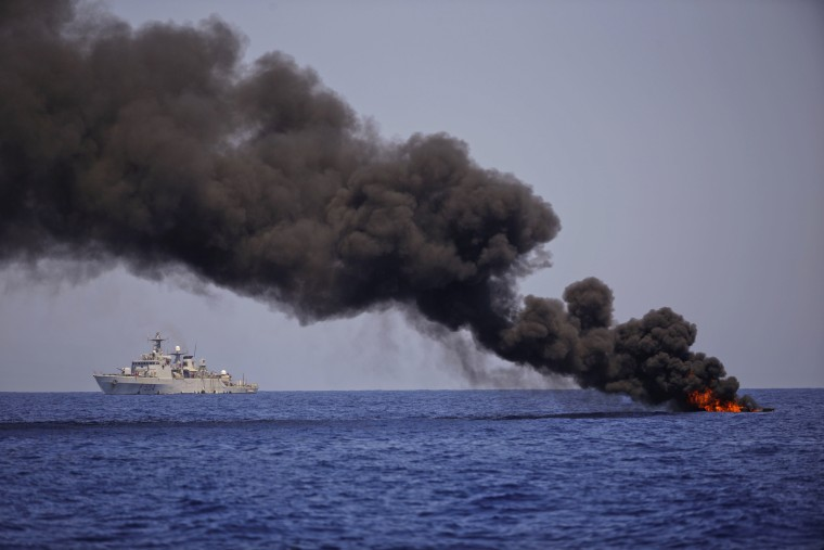 Image: An Italian Navy ship sails past a burning dinghy after evacuating the migrants sailing on it