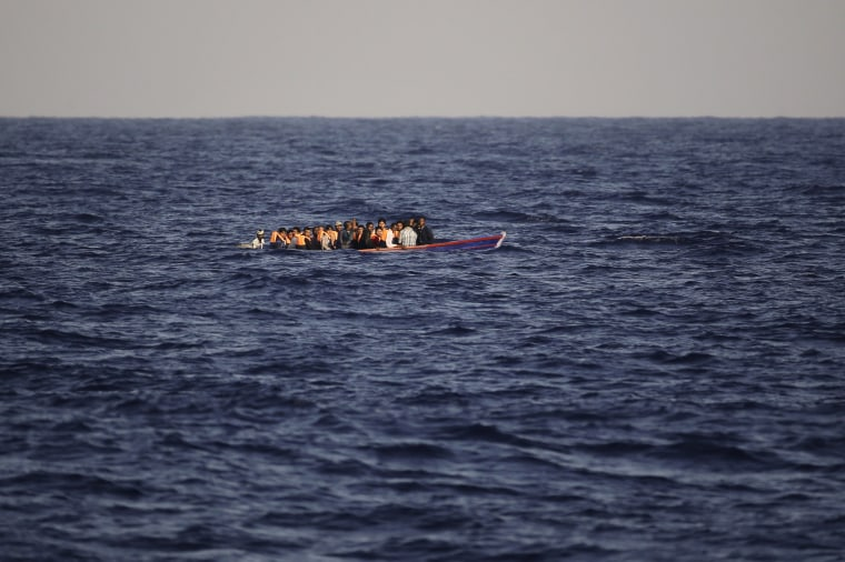 Image: Migrants and refugees flee Libya on board of a wooden boat.