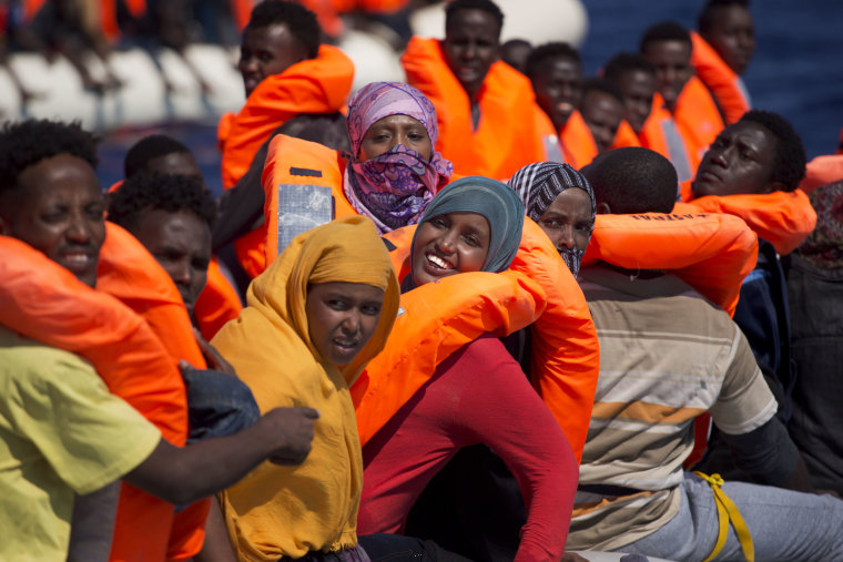 Image: Migrant women smile on board of a dinghy as they sail in the Mediterranean sea