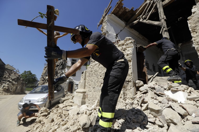 Image: Firefighters retrieve a crucifix from a church in the small town of Rio