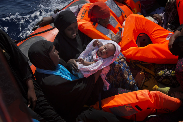 Image: Migrant women from Nigeria, one of them holding a baby, are rescued by emergency teams