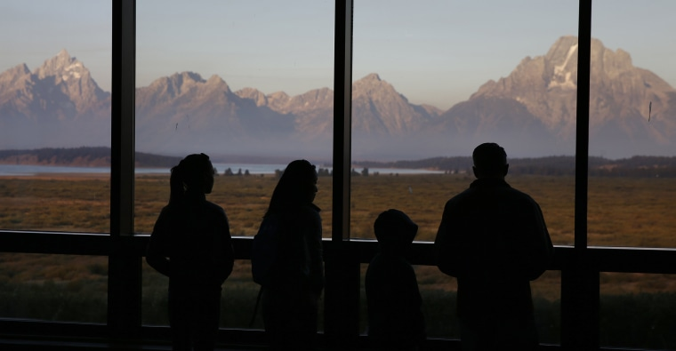 Image: Visitors watch the morning sun illuminate the Grand Tetons