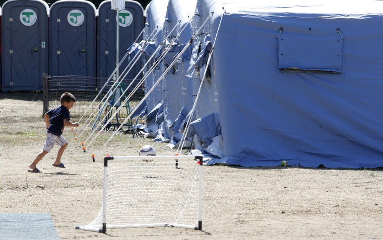 Image: A child plays in a tent camp in Amatrice