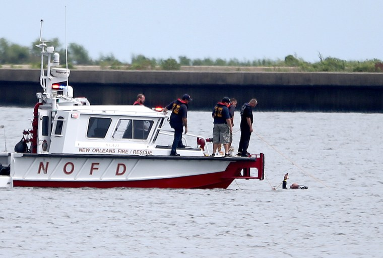 A diver in the water signals to a New Orleans Fire Department boat while searching for the wreckage Sunday, Aug. 28, 2016, near the Seabrook Bridge after a plane crashed into Lake Pontchartrain Saturday night near Lakefront Airport in New Orleans.