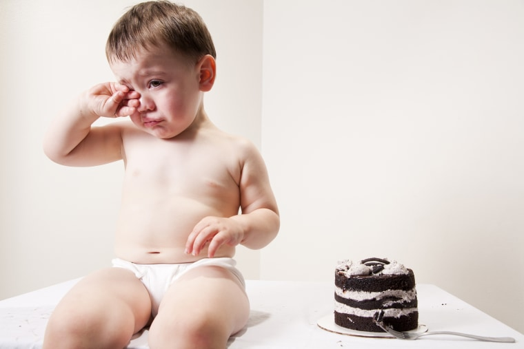 Chubby baby crying over cake