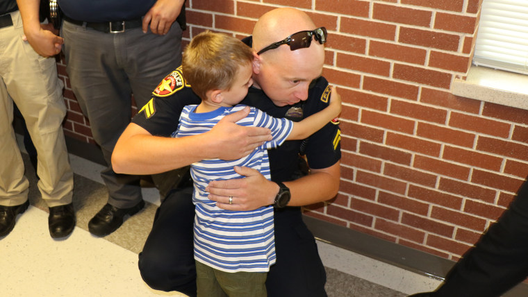 police officers surprising the children of an officer who died by walking them to the first day of school