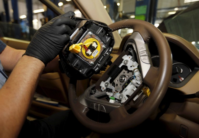Image: File photo of Technician Bonilla holding a recalled Takata airbag inflator after he removed it from a Honda Pilot at the AutoNation Honda dealership service department in Miami