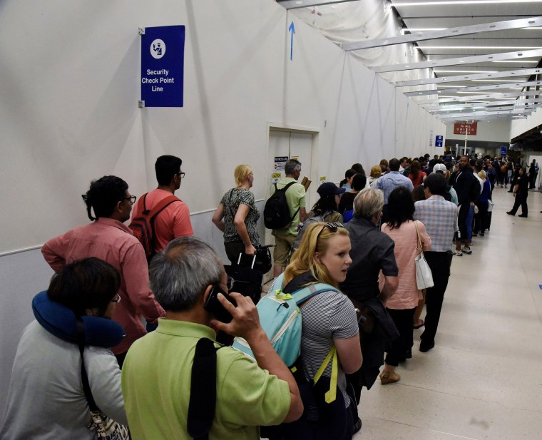 Image: Delayed passengers inside Terminal 7 at Los Angeles International Airport go through TSA security check following a false alarm event in Los Angeles