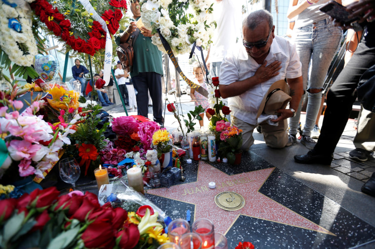 Image: Manuel Solis pauses by the star of late Mexican singer Juan Gabriel, which is adorned with flowers and mementos, on the Hollywood Walk of Fame in Los Angeles